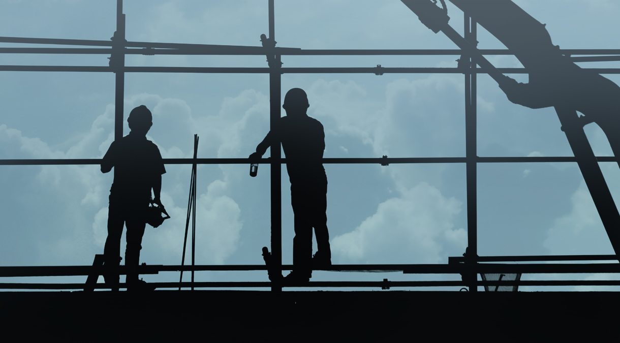 Two construction workers standing on scaffolding.